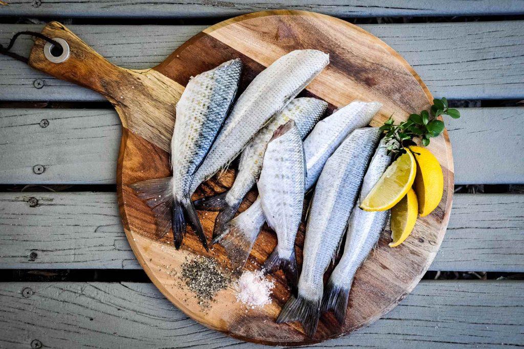 köp hem färsk fisk via fiskbilen bild på träbräda med färska fiskar och kryddor